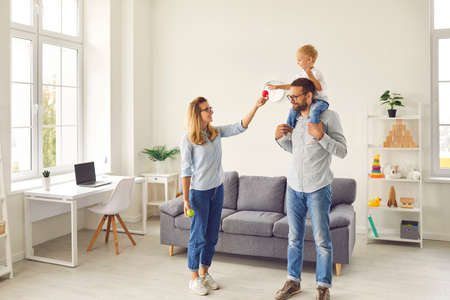 Happy young family of mom, dad and little son spending quality time at home, enjoying weekend, playing fun games with balls together in the light cozy living-room of their new house or apartment