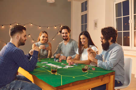 Having fun together. Group of happy young friends in casual clothes playing poker sitting at table with some drinks during casino themed party at home Banco de Imagens