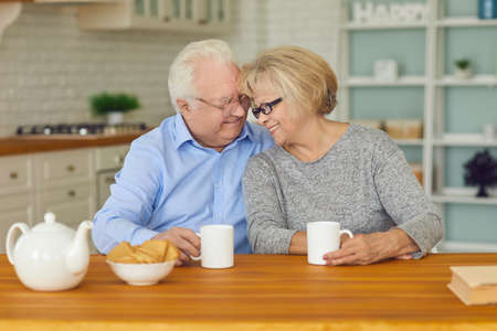 Cherish your loved ones. Happy senior couple sitting at kitchen table at home, drinking tea with cookies, hugging each other. Portrait for Saint Valentines or International Day for Older Persons