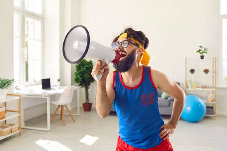 Funny eccentric bearded trainer man dressed in brightly colored sportswear glasses shouts loudly into loudspeaker urging everyone to exercise. Concept of fun active comic lifestyle.