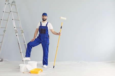 Young smiling professional worker or painter in special blue uniform standing with paint roller in hand near ladder and looking at camera in new apartment for repairing over white walls background.
