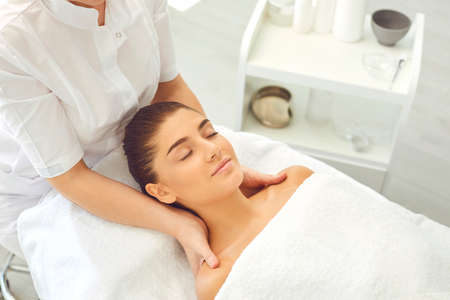 Good looking young woman lying on bed in beauty parlor with eyes closed enjoying face and neck massage done by professional massagist. Female client getting skincare procedures