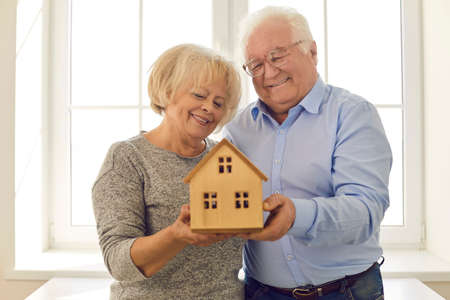 Portrait of happy smiling elderly couple holding small wooden house standing by the window in their new home. Concept of real estate and senior citizens buying property insurance