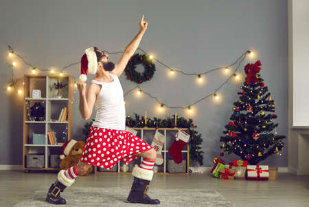 Loud neighbor in funny underpants and boots wants to dance and party hard, locked down in quarantine at home on Christmas holidays. Happy Santa announces start of big New Year sale deals and bargains