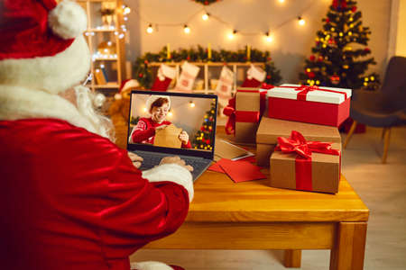 Christmas wish is sure to come true. Over shoulder Santa Claus sitting at desk, looking at laptop computer screen spying on little child whos writing and sending letter in which he asks for a present