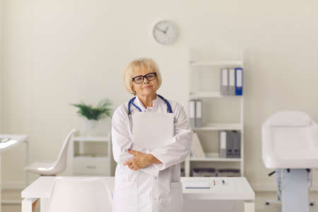 Portrait of experienced mature woman doctor standing in hospital office holding clipboard and looking at camera. Healthcare, senior clinic staff, professional medical help, therapeutic expertise