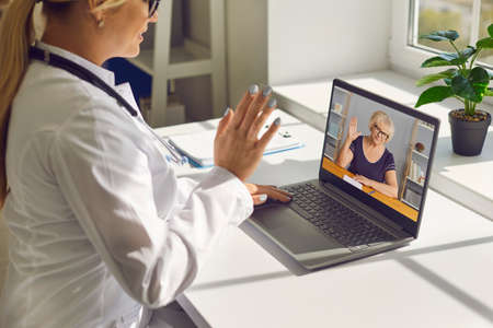 Telemedicine and e-health services. Closeup of doctor waving hand at computer screen greeting senior woman at online consultation. General practitioner using laptop to video call mature patient