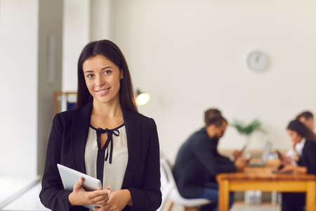 Happy smiling female company president holding tablet computer standing in office looking at camera. Portrait of young woman, successful business leader, in office workspace with busy employees behind Archivio Fotografico