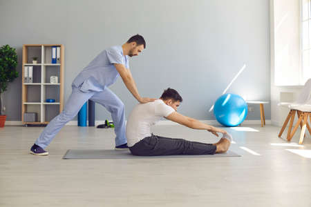 Professional man chiropractor or osteopath stretching man patients back and making rehabilitation theapy for patient during visit in manual therapy clinic. Chiropractor during work concept