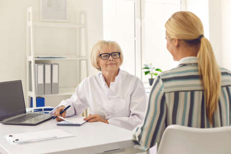 Competent senior doctor prescribing treatment for female patient sitting at desk in hospital office. Happy young woman thanking professional mature physician for help during check-up in modern clinic