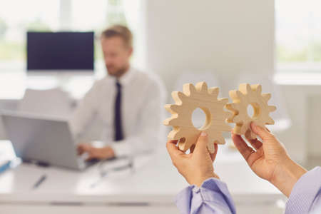 Close up of woman's hands holding round wooden figurines on the background of office worker. Woman invites a man to a training or game to improve results at work. Business control and management concept Stockfoto