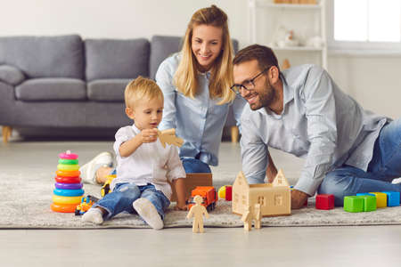 Happy family at home. Young mom, dad and their little child playing games with wooden dolls and blocks on warm floor of their living-room, enjoying weekend, spending quality time together at home
