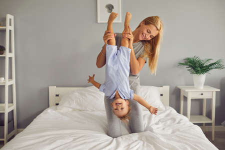 Happy carefree family having fun at home. Smiling mother and laughing little child enjoying weekend together playing on comfy bed in cozy bedroom. Young mom holding funny brave toddler son upside down 版權商用圖片