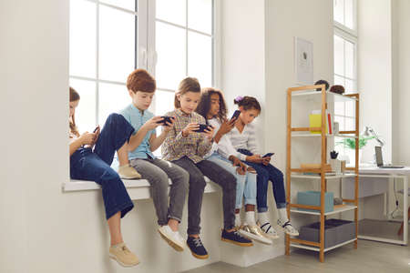Diverse group of 8-10 year old children sitting on windowsill, playing online phone games and ignoring each other. Concept of gadget addiction and excessive use of social media and mobile devices