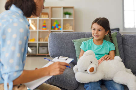 Supportive psychologist with clipboard talking to little girl. Therapist and happy child communicating, analyzing behavior and solving problems during therapy session in cozy modern office