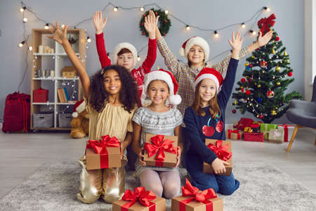 Portrait of various cheerful children in Christmas hats and with gifts they received on Christmas day. Children raise their hands up looking at the camera in a cozy room with bright Christmas decor.