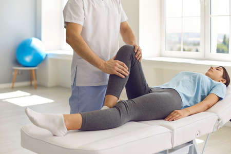 Woman in modern clinic doing medical physical exercise with qualified specialist. Cropped physiotherapist examining patients leg to reveal problem and assign therapy after sports injury