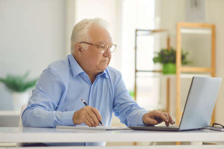 Serious senior man in glasses sitting at desk at home, using laptop computer and taking notes with pencil, studying new information online, managing budget, calculating expenses, paying utility bills