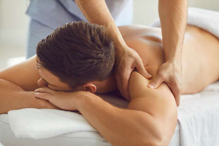 Close-up of relaxed young man lying on massage table enjoying remedial body massage done by professional masseur in modern wellness or health center