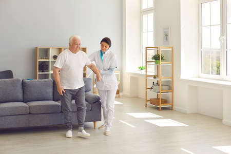 Recovery is easier with the right support. Friendly nurse helps an elderly patient walk around the room in a nursing home holding his hand. Concept of medical care and nursing.