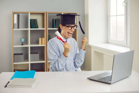 Happy excited college or university student sitting at desk with laptop, holding diploma and celebrating success as she graduated with excellent grades, managed to get good job or win research grant