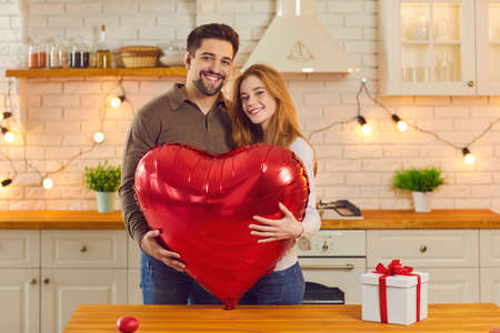 Cute smiling couple standing in kitchen holding huge shiny red heart-shaped balloon. Happy young woman enjoying romantic presents and surprises at anniversary or Valentines Day party with boyfriend