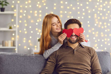 Happy smiling couple in love celebrating their relationship anniversary at home. Young people having fun on Saint Valentines Day. Woman covering boyfriends eyes with two red heart-shaped cards