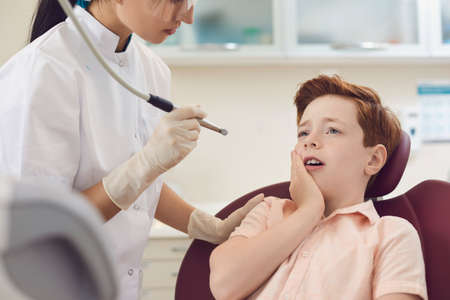 Little timid boy sits in dentist chair and puts his hand to his cheek suffering from severe toothache. Concept of pediatric dentistry health and dental care.