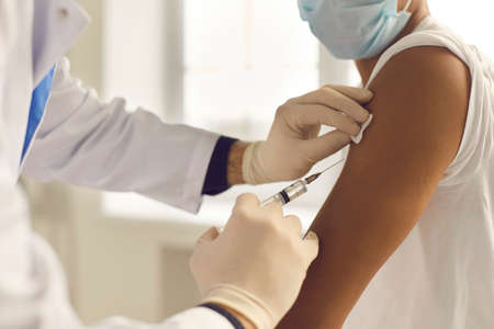 Doctor in medical gloves giving Covid-19, AIDS or flu antivirus vaccine shot to African-American patient. Close-up of hands holding syringe and cleaning skin on upper arm before antiviral injection