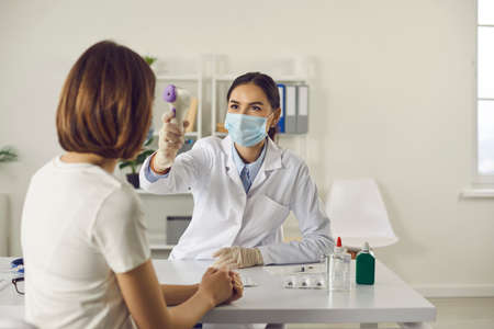Young nurse or doctor in medical face mask taking patients body temperature with non-contact infrared thermometer. Woman gets temperature measured during visit to hospital for flu or Covid-19 vaccine