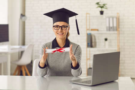Remote education. Online degree course. Talented student in mortar board and glasses sitting at desk with laptop computer, holding diploma or graduate certificate scroll, smiling and looking at camera