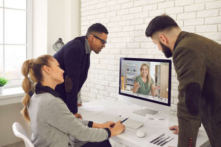 Company staff having virtual business communication and online meetings. Group of young diverse people looking at computer screen during video call with coworker, executive manager, client or mentor