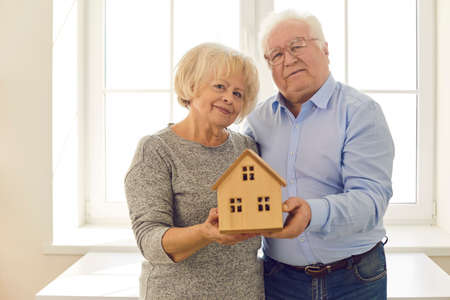 Portrait of happy smiling senior couple holding small wooden house standing by the window in their new home. Concept of older citizens buying property insurance