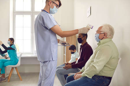 Hospital worker measuring senior patients body temperature with non-contact electronic thermometer. Old and young multiracial people in medical face masks waiting to get vaccine at doctors office