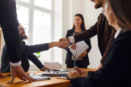 Young business people closing a deal and shaking hands after a successful negotiation meeting in the office. Partnership, mutual help, trust and cooperation concepts Banque d'images