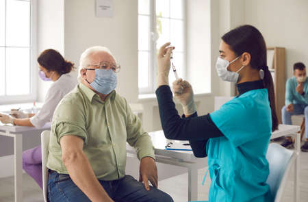 Antivirus vaccination for older people. Covid-19, pneumonia or flu preventive measures. Male senior citizen waiting to receive his vaccine. Asian doctor in face mask administering shot to mature man