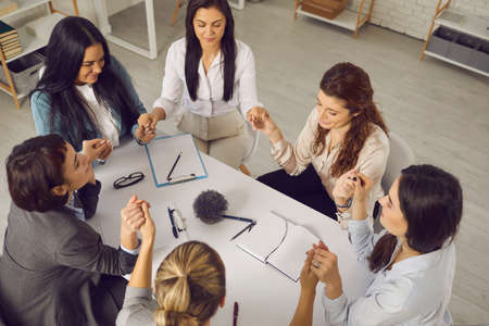 Team of business women holding hands, sitting together around office table with eyes closed in group meeting or coaching session. Support, unity, understanding, empathy concept. From above, high angle