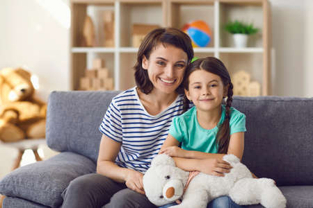 Portrait of happy kid girl and smiling mother looking at camera webcam making online call. Caring mother hugs her daughter and talks to relatives in a video chat.