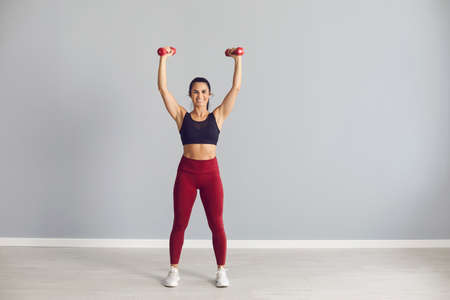 Lifestyle. Portrait of a beautiful athletic woman standing with raised dumbbells in her hands and showing off her toned athletic body. Woman in sports uniform posing on a background of gray wall. Foto de archivo