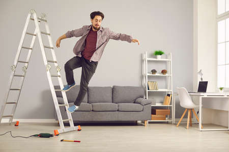 Unlucky young man has slipped from ladder while doing repairs and renovating house and is falling down on floor. Concept of getting hurt and injured in dangerous domestic accidents at home