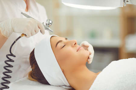 Close-up of young smiling woman getting oxygen therapy or jet peeling from cosmetologist with special equipment in beauty spa salon, side view. Oxygen therapy in cosmetology