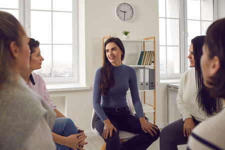 Young woman sharing her story with other ladies in therapy session or support group meeting. Female friends talking, discussing life situations, giving advice and helping each other cope with problems