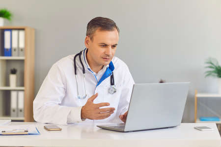 Male family doctor uses a laptop to conduct an online consultation with his patient while sitting in office. Doctor in a medical gown explains the patients diagnosis and calls for urgent treatment.