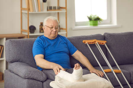 Rehabilitation after domestic or car accident injury: Senior male stays at home, waiting for bone fracture to heal. Old man with broken leg in plaster cast sitting on sofa with crutches in living-room