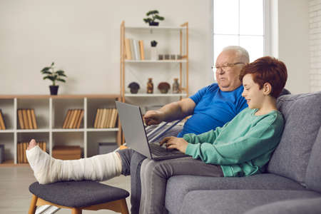 Happy relaxed senior man with broken leg in plaster cast spends fun time using laptop, watching movie or playing online game together with grandson. Recovery after injury. Familys help and support Standard-Bild