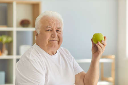 Food thats good for health. Senior holding green apple, motivating you to keep healthy diet in old age. Mature man recommends eating raw fruit and reminds that an apple a day keeps the doctor away