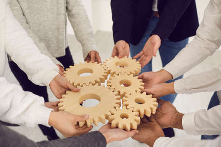 Cropped shot of group of multiethnic people joining gear wheels together as metaphor for team collaboration, unity, teamwork, finding creative solutions and creating well-functioning business system
