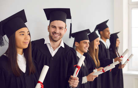 Happy student man with diploma in hands looking at camera standing next to his multiethnic classmates friends. Group of people in graduation gowns standing in a row near the wall in the classroom.