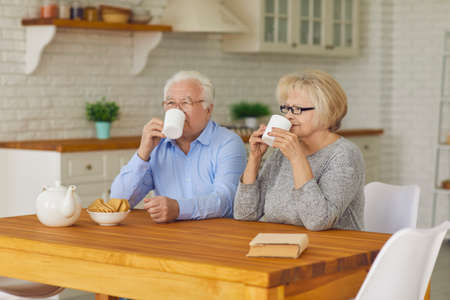 Side view of a senior couple with cups in their hands in the morning sitting in the kitchen drinking tea or coffee. Elderly man and woman watching TV positively start the day with hot drinks.