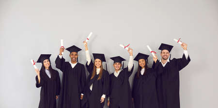 Study abroad website banner. Group of happy smiling diverse academy graduates holding up diplomas. International university students in traditional black academic gowns and caps celebrating graduation